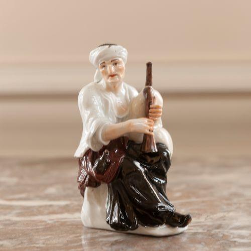 Sujet en porcelaine figurant un jeune joueur de cornemuse.  Modèle de Kaëndler. …