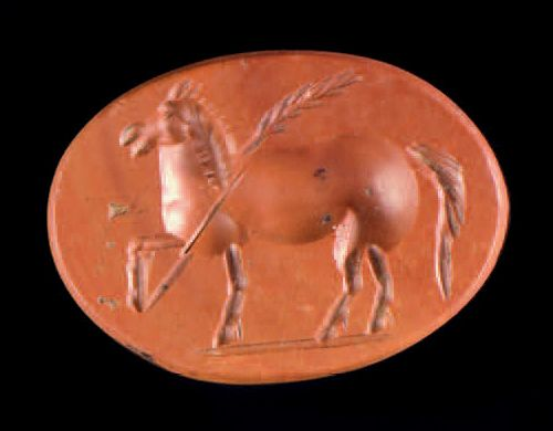 Flat oval intaglio engraved with a horse passing on the left in front of a branc…