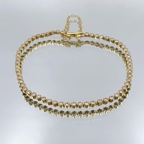 BRACELET in yellow gold (750%) set with an alignment of white stones. French wor…
