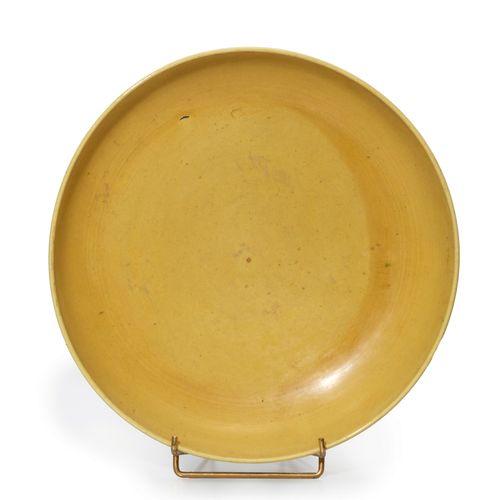 CHINE Grande assiette recouverte d'une glaçure jaune pâle, s'arrêtant au pied .A…
