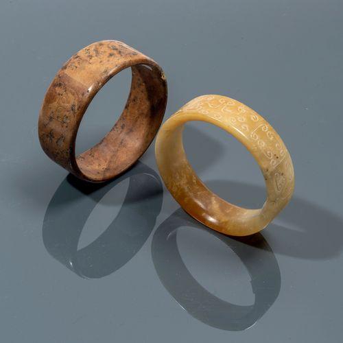 CHINE De style Ming Deux bracelets, l'un en néphrite brune à décor de têtes de f…