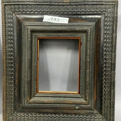Blackened moulded wooden frame with an upside down profile and decorated with gu…