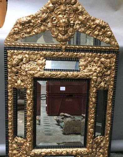 Mirror with blackened wood brackets richly decorated with gilded embossed metal…