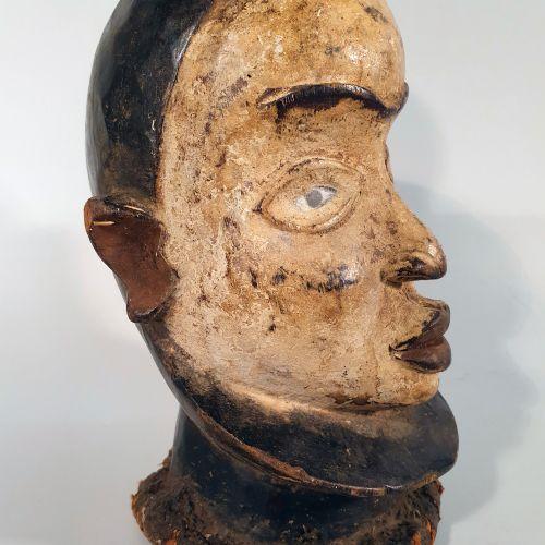 Afrique. Jolie tête recouverte de caolin sur la face et d'une patine sombre sur …