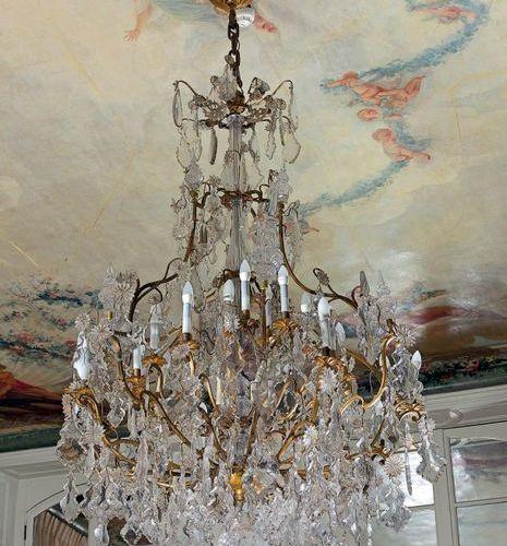 Très grand lustre en bronze doré à trente deux lumières sur trois rangs, orné de…