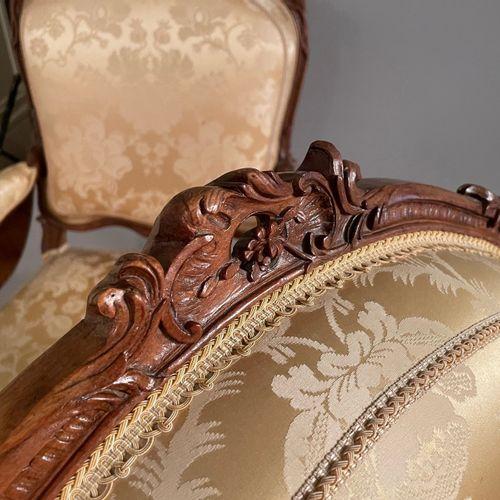 Suite de six fauteuils à dossier plat en noyer sculpté et ajouré de fleurs. Epau…