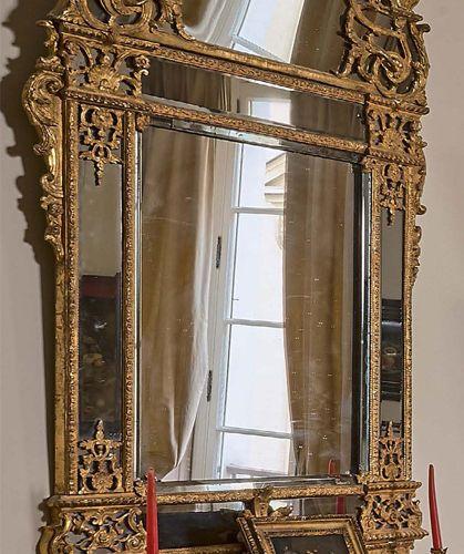 Miroir biseauté dans un double encadrement à fronton en bois redoré sculpté de c…