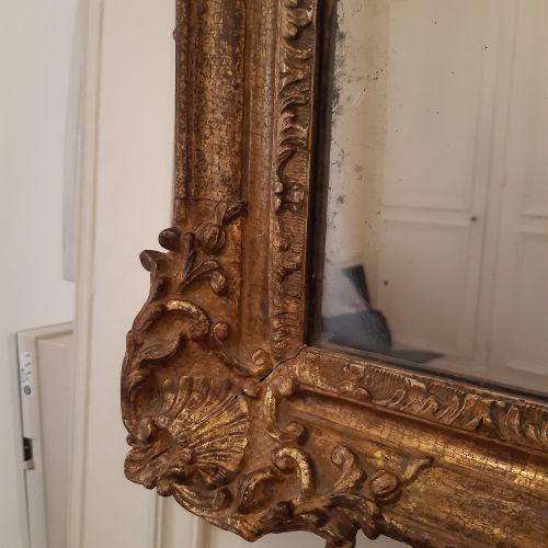 Miroir dans un encadrement en bois doré à fronton ajouré sculpté d'une grenade e…