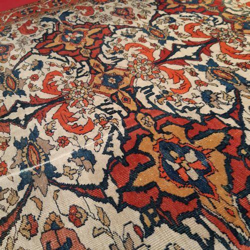 Tapis persan orné de rinceaux feuillagés stylisés sur fond blanc. Bordure à fond…