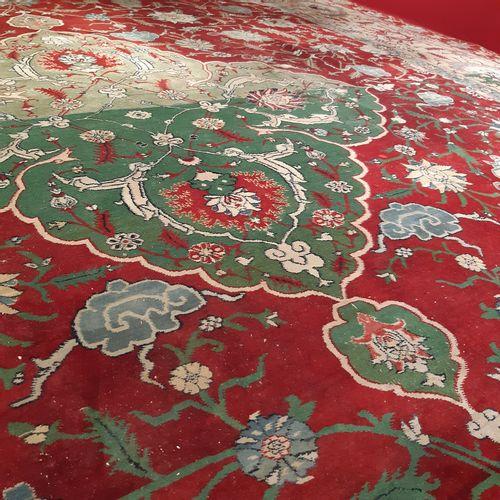 Grand tapis orné d'un médaillon polylobé vert sur un fond rouge à écoinçons, orn…