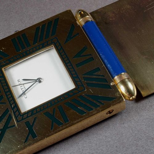 CARTIER MUST. Pendulette de voyage en laiton et laque bleu sur plaque articulée.…