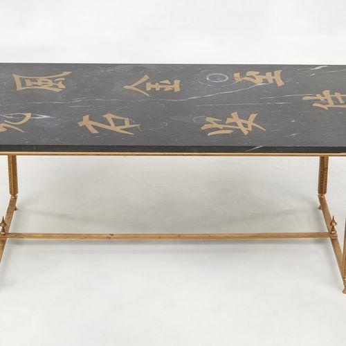 Circa 1960. Meuble: Table basse au piétement de laiton et tablette de marbre noi…