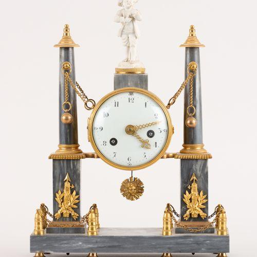 D'époque Louis XVI. 发条:一个绿松石的大理石台钟,柱子的图案支撑着珐琅彩表盘机芯,有不对称的上弦器和鏤空的指针,上面有一个饼干瓷的爱情雕塑(…