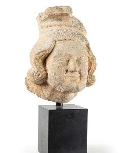Limestone corbel carved with a man's head; medium long wavy hair with curved end…