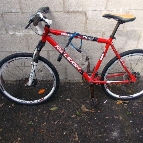 VTT Rockrider RR 5.2, noir, pneus usés. VTT Raleigh, rouge et blanc, traces de r…